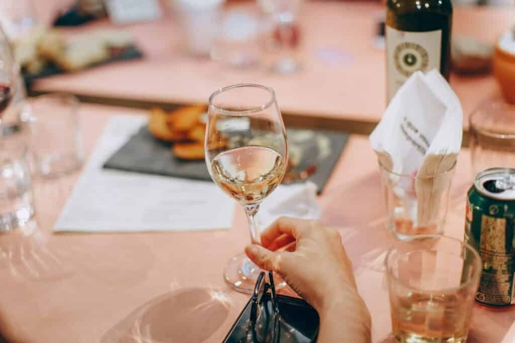 Glass of wine being held over pink table