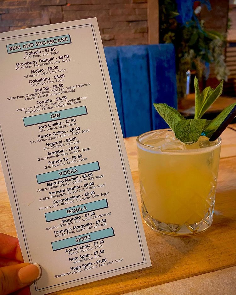 Someone holding The Catch Sheffield menu next to a cocktail