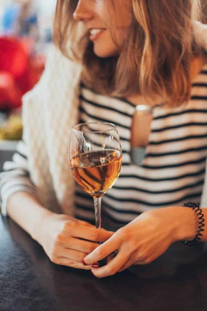 Woman with stripy t-shirt drinking wine in Vinyard