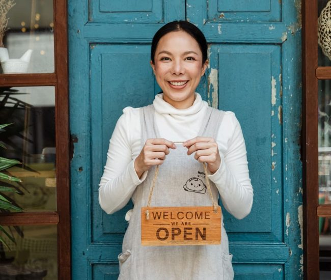 Shop owner holding open sign for Samdai
